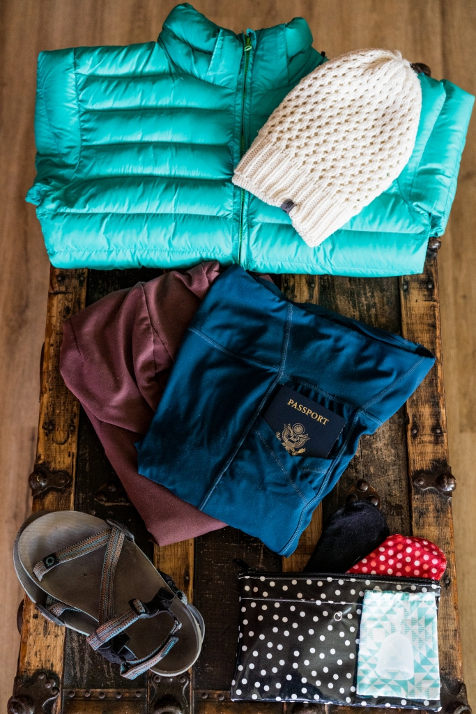 A turquoise puffy coat, a white beanie, a pair of sandals, a passport, yoga pants, and reusable period products.