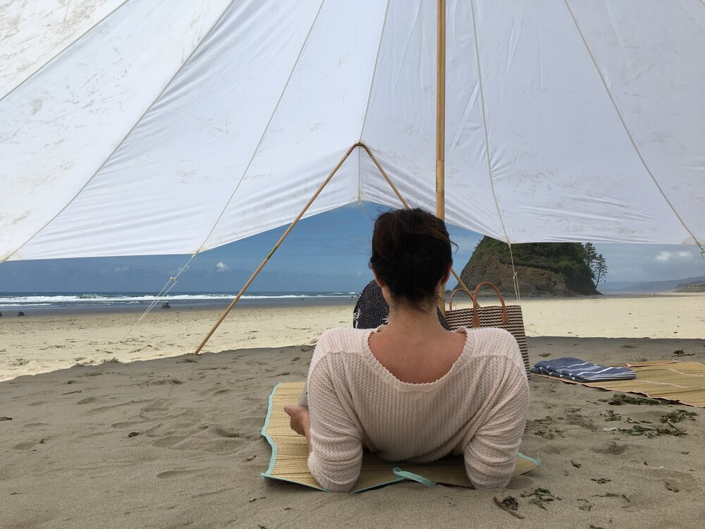 A person leans back on their elbows beneath a shade canopy on the beach.