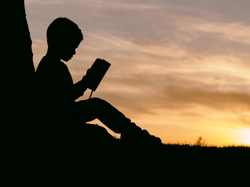 Silhouette of a child reading at sunset.