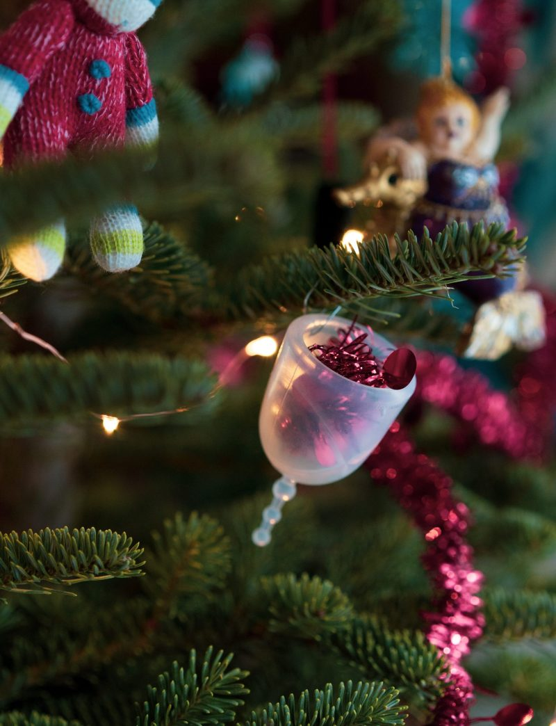 An XO Flo menstrual cup hangs like an ornament from a Christmas tree.